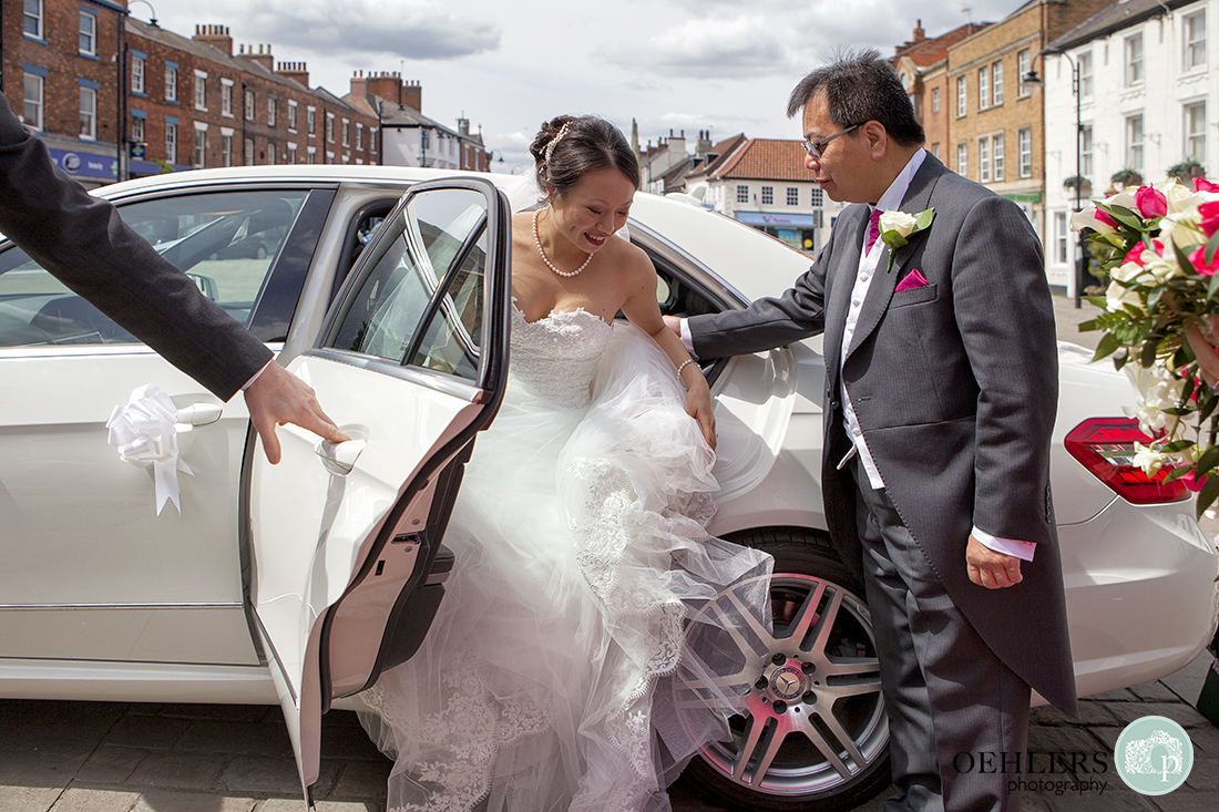 Bride arrives in her wedding car with father helping her out of the car.