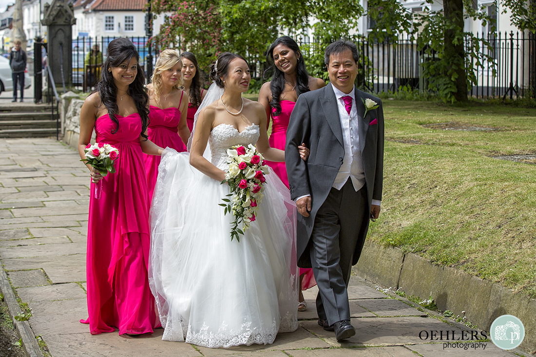 Bride and father walking arm in arm down the path leading to Selby Abbey with Bridesmaids holding the train.