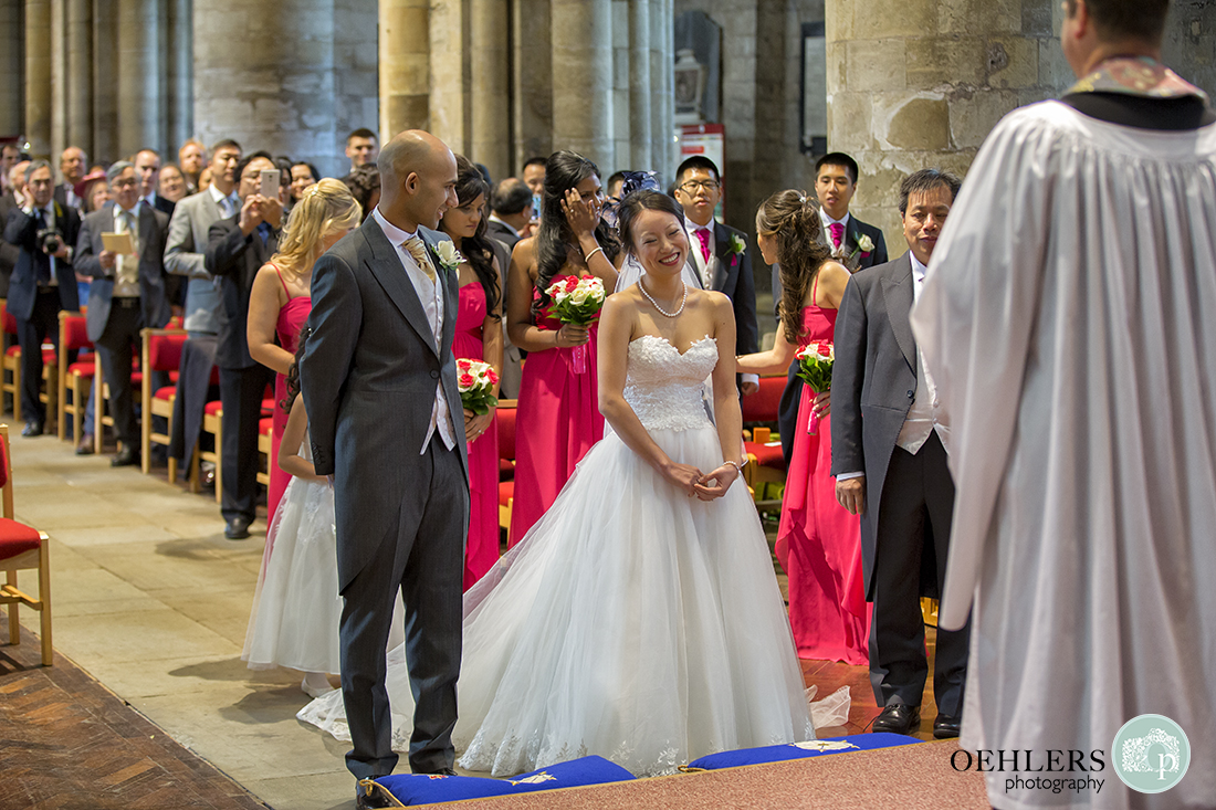 Happy bride arrives at the altar in Selby Abbey with the Groom smiling at her.