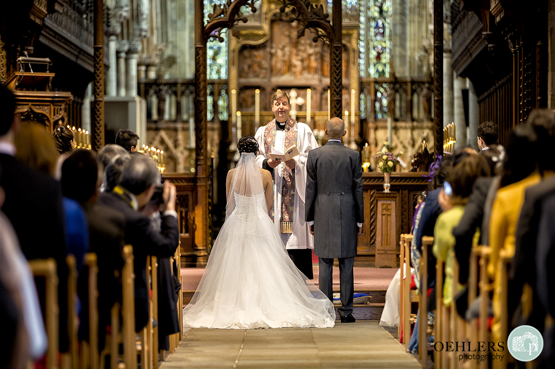Looking down the aisle at the Bride and Groom in front of the clergyman ready to take their wedding vows.