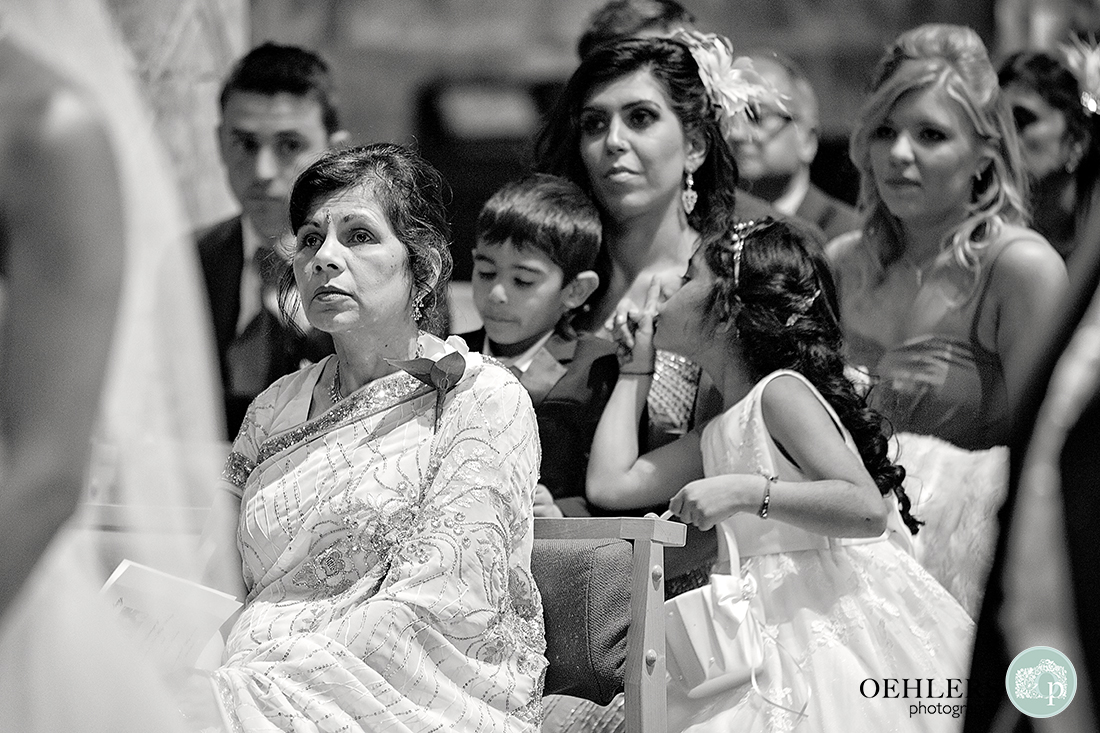 Black and White Photograph of the congregation with young flowergirl telling her brother to keep quiet.