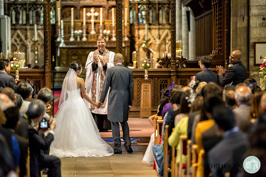 Photograph taken from the back of the congregation applauding the Bride and Groom.