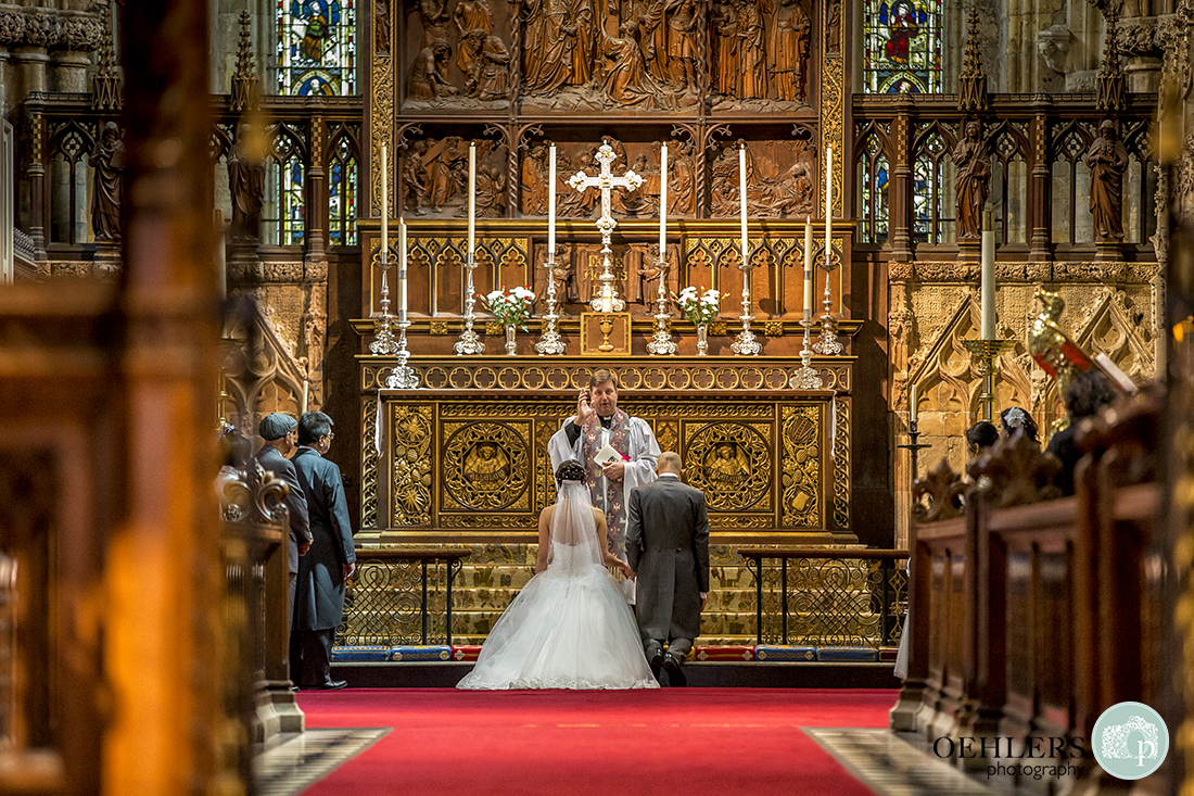 Bride and Groom kneeling at the intricately carved altar having their blessing.