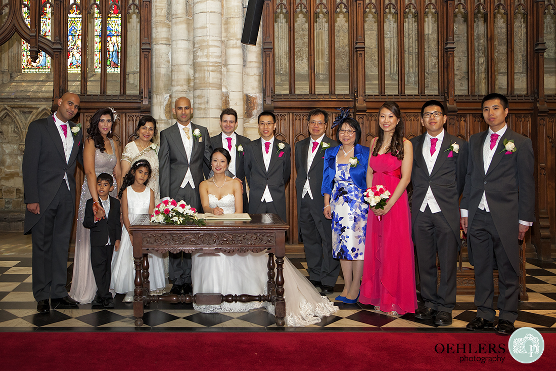 Formal group photograph of the bride and groom at the registry table with the family members.