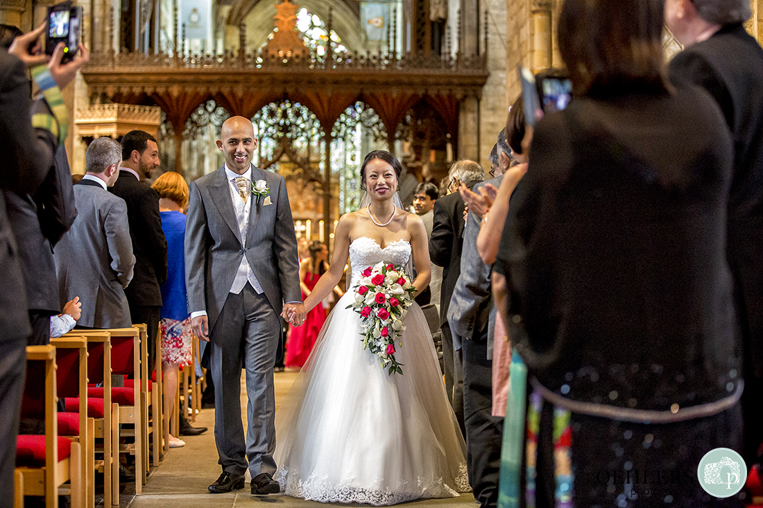 Happy Bride and Groom walking back up the aisle at Selby Abbey whilst the congregation take photographs.
