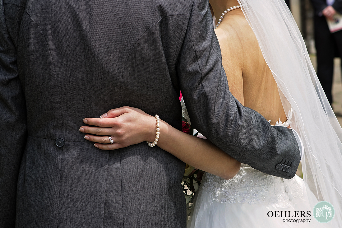 Touching close up photograph of brides hand on the groom's back whilst his arm is around her waist.