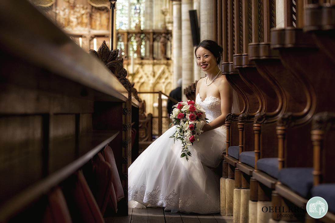 Beautiful portrait of bride sitting on a pew.
