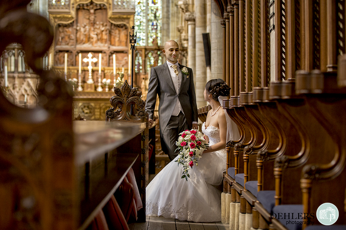 Photograph of the groomstanding and looking at the bride sitting in the pews.