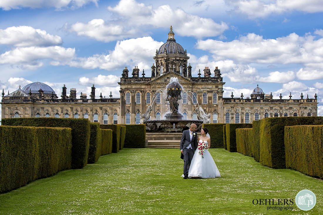 Bride and Groom walking in between yew hedges towards camera with Castle Howard in the backgroud.