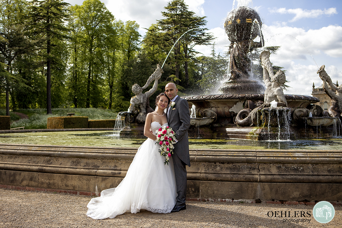 Formal photo of Bride and Groom posing in front of the Atlas Fountain at Castle Howard.