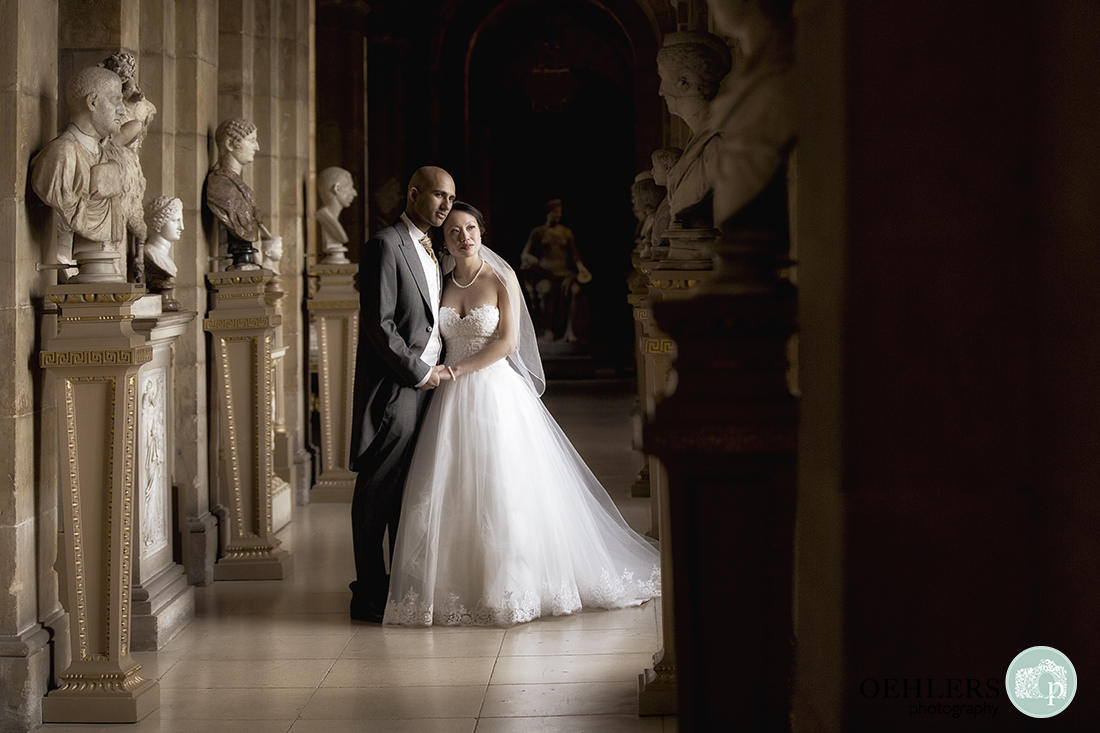 Bride and Groom posing inside the Antique Passage at Castle Howard lined with busts and figurines.