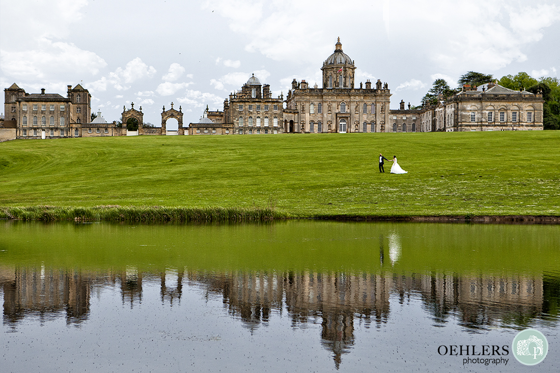 Reflection of Bride and Groom in the lake in front of Castle Howard as they walk from right to left across the grounds.