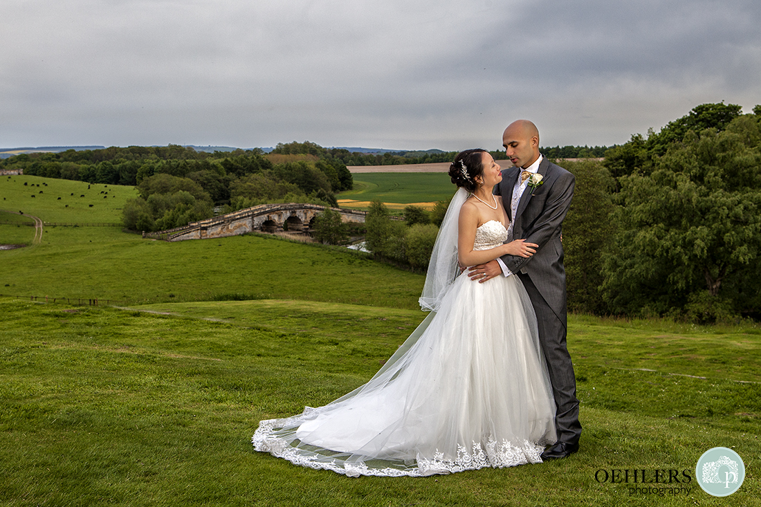 Lovely photograph of the groom and bride standing, looking at each other with a bride and open countryside behind them.