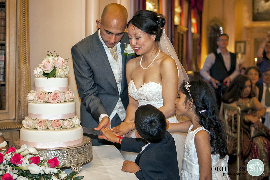 Bride and Groom cutting their wedding cake with flower girl and a boy helping.