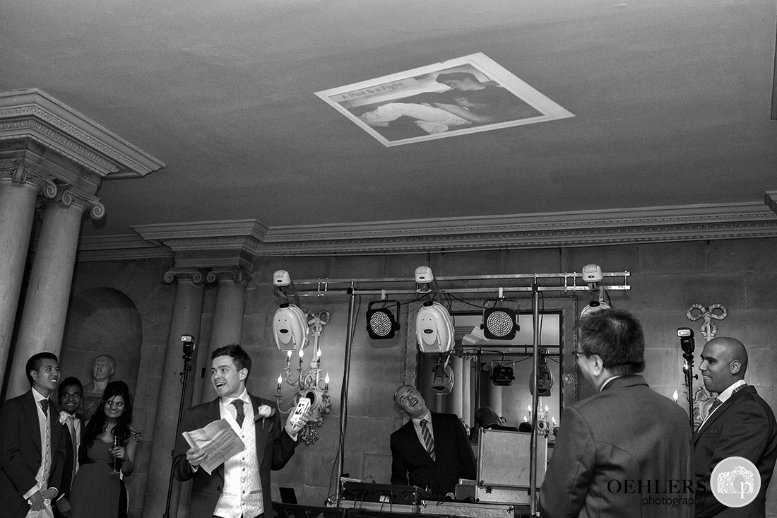 Bestmen projecting an image onto the ceiling whilst making a speech.