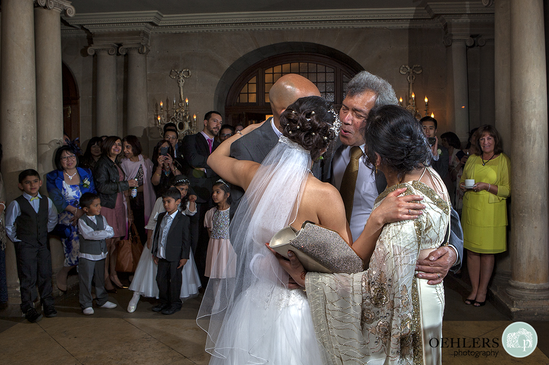 Some family members congratulate the Bride and Groom after the first dance by a huge hug with guests looking on.