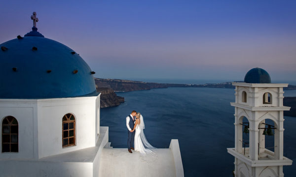 Nottingham Wedding Photographers-Bride and Groom on top of a church building overlooking the caldera in Santorini.