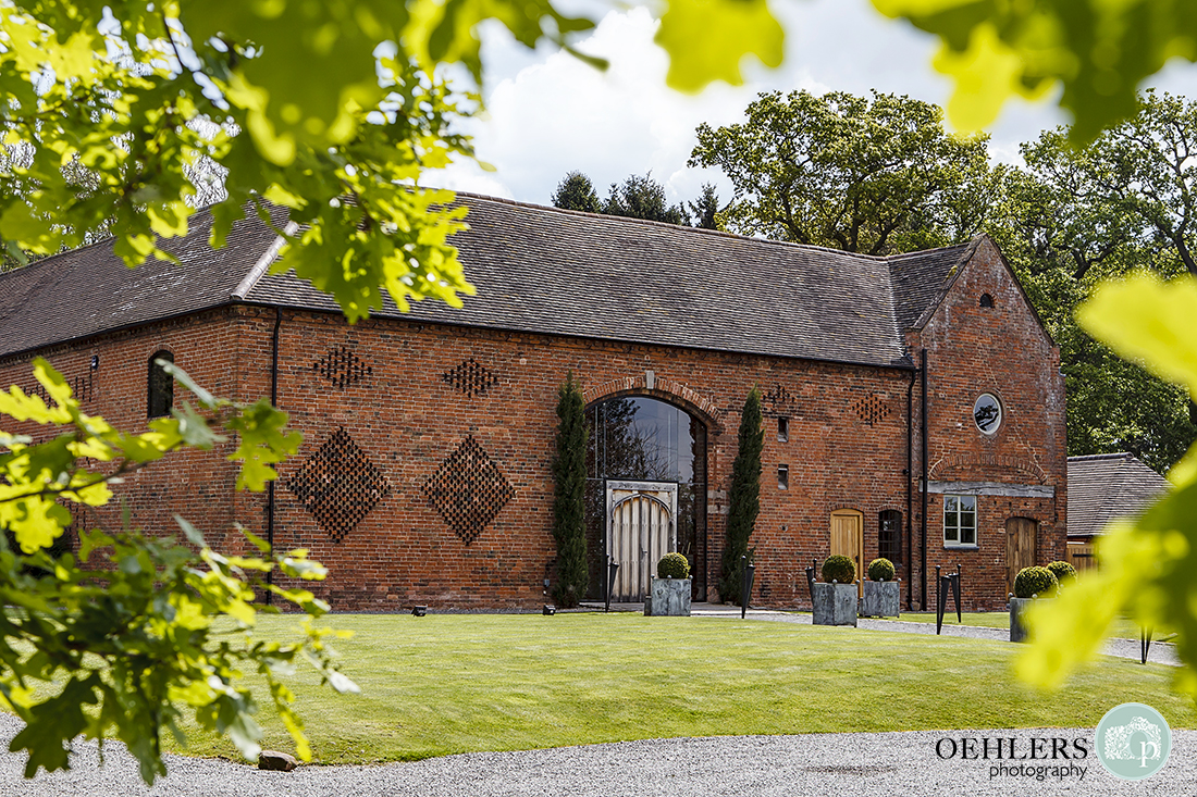 Front facade of sunny Shustoke Barn, Coleshill through leafy vignette.