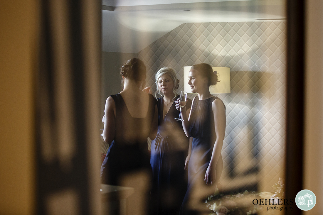 Reflection of bridesmaids in their satin dresses drinking champagne.