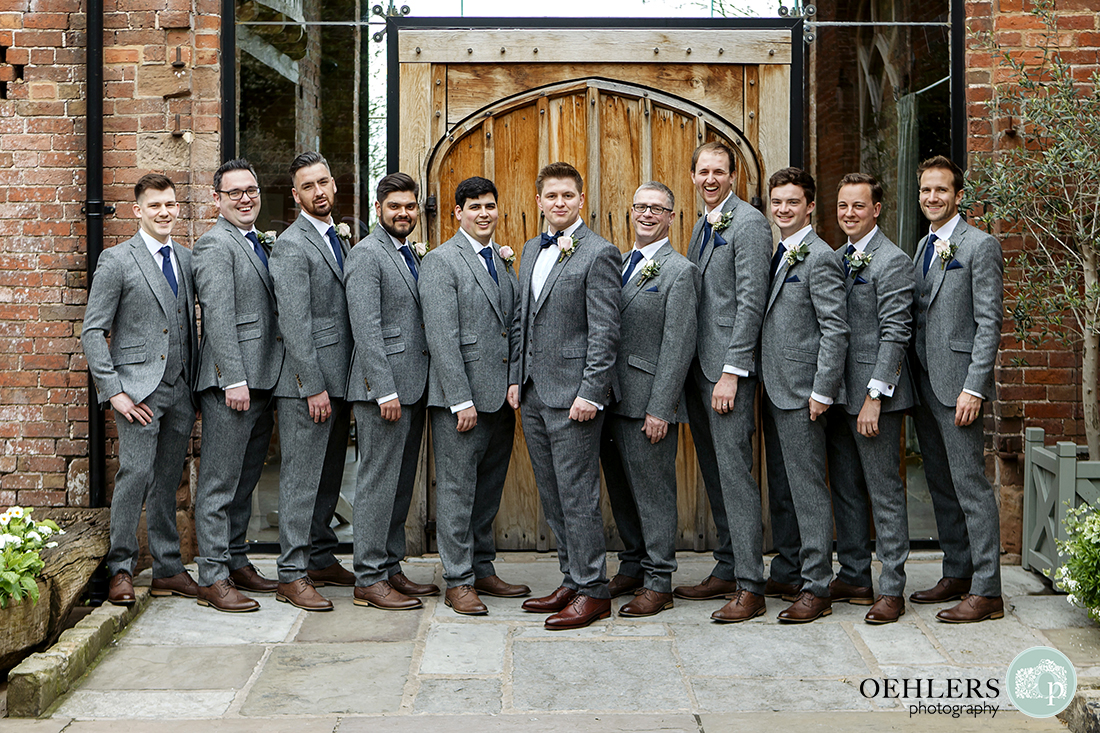 Groom, groom's father, bestman and groomsmen striking a pose in the courtyard at Shustoke Barn.