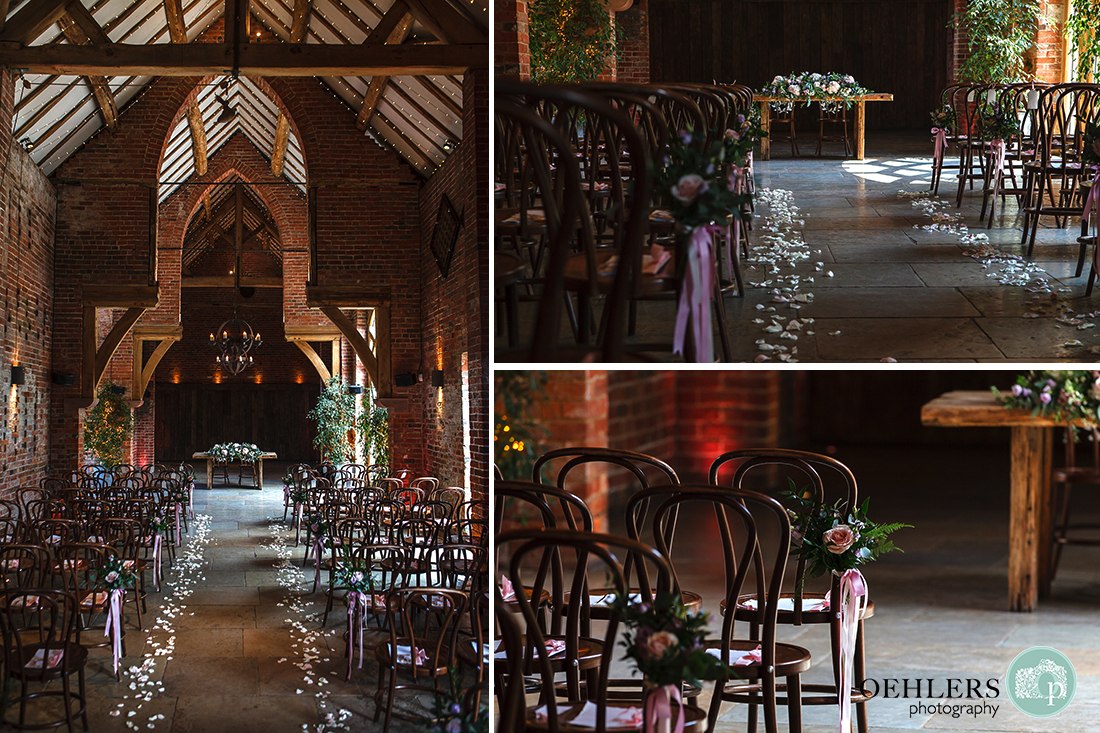 Shustoke Barn wedding ceremony room showing rose petals strewn down the sides of the aisle and roses on chair-sides.