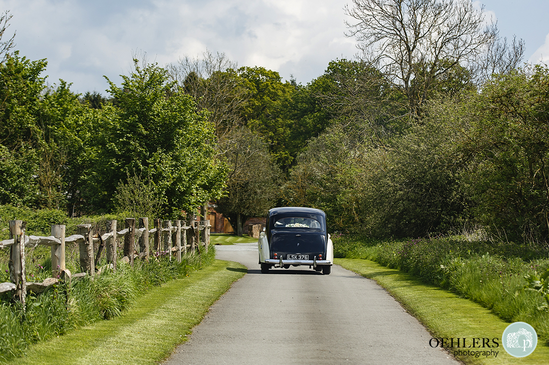 Sleek Rolls-Royce wedding car proceeding along manicured driveway to the venue.