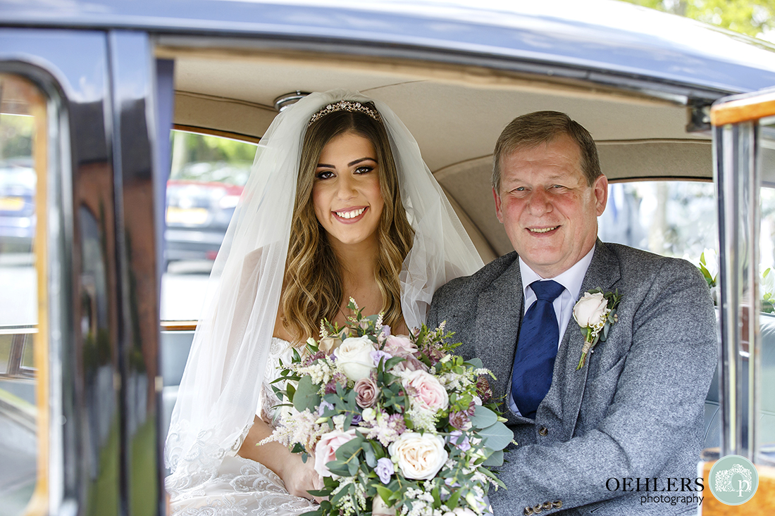 Smiling bride holding bouquet with her father framed in doorway of the wedding car.