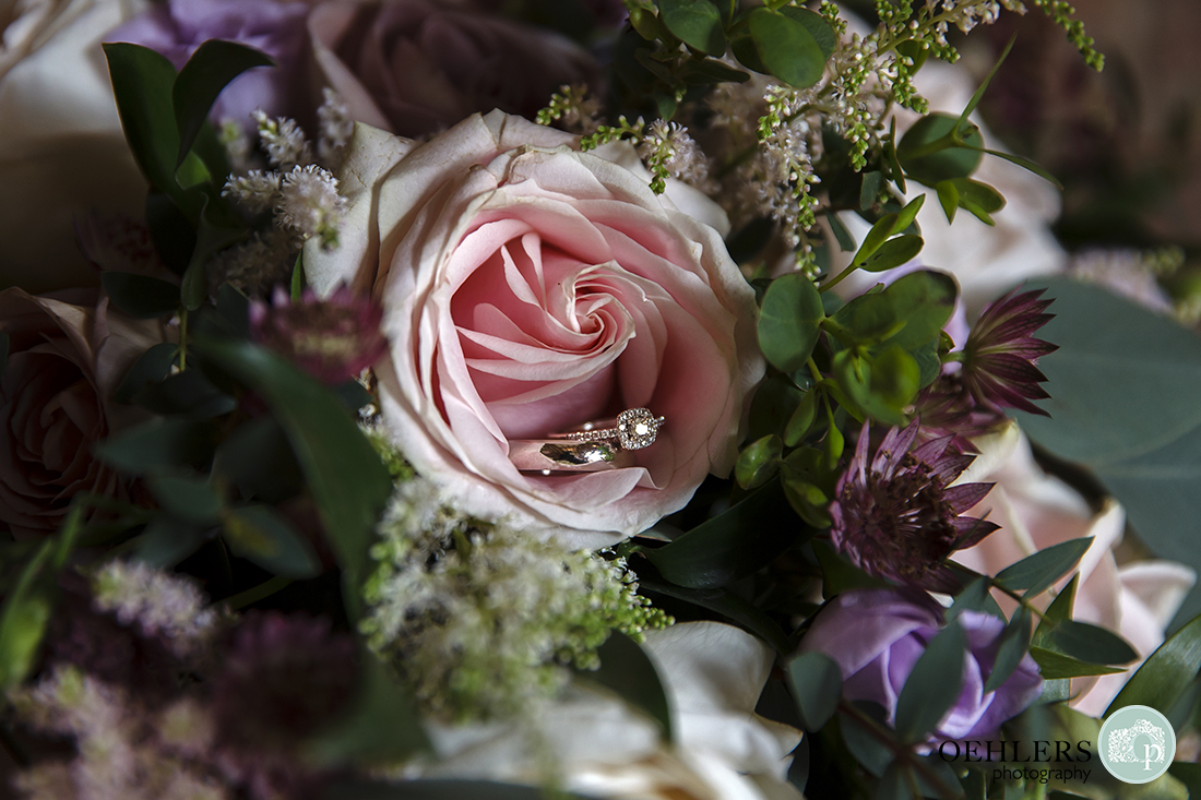 Close-up photograph of the wedding rings in a beautiful, delicate blush-pink rose on the bride's bouquet.