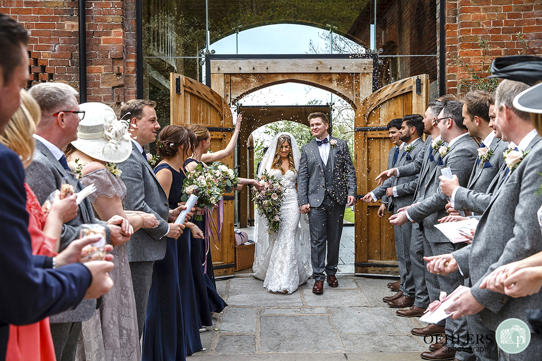 Guests lined up in the courtyard throwing confetti at the happy couple.