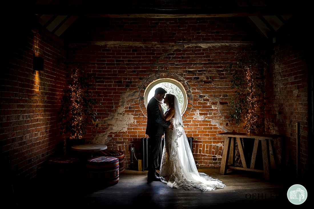 bride and groom embrace semi-sihouetted in the sunlight streaming in to a rustic room at the venue.