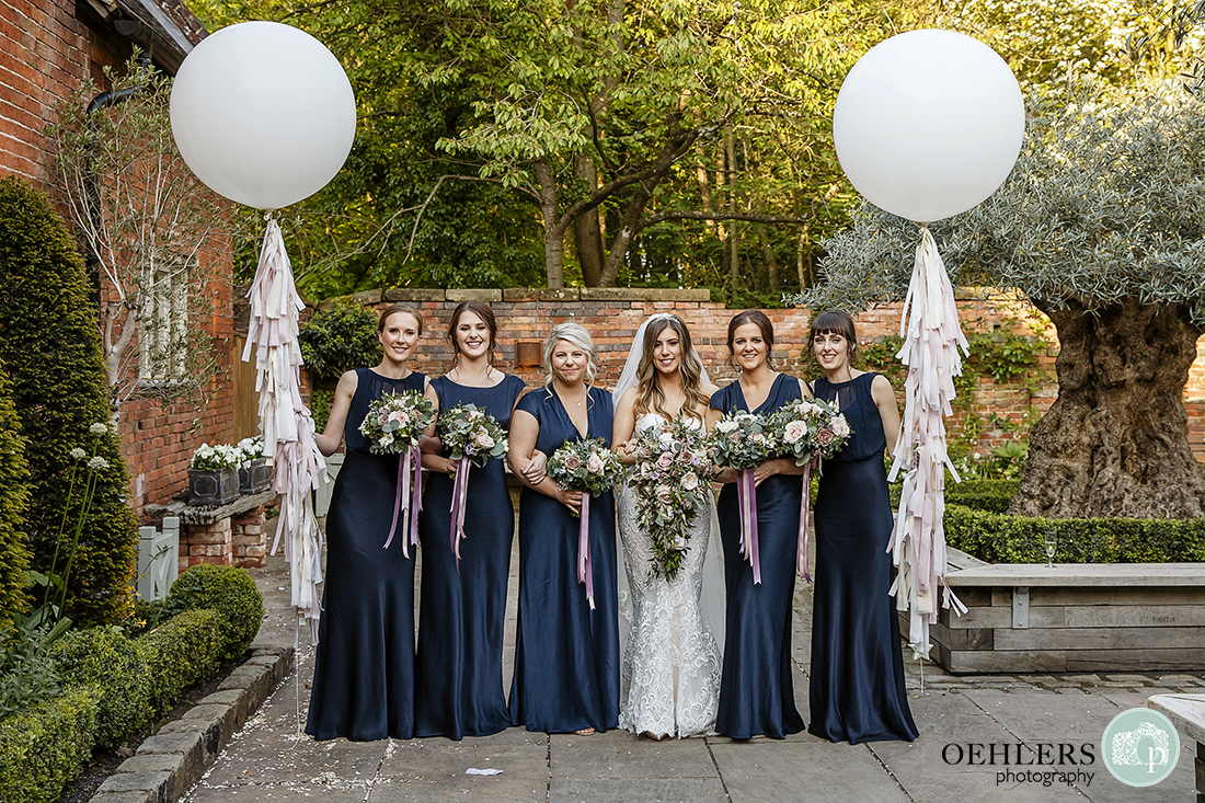 Bride and bridesmaids pose in courtyard flanked by two large white balloons on decorative strings.