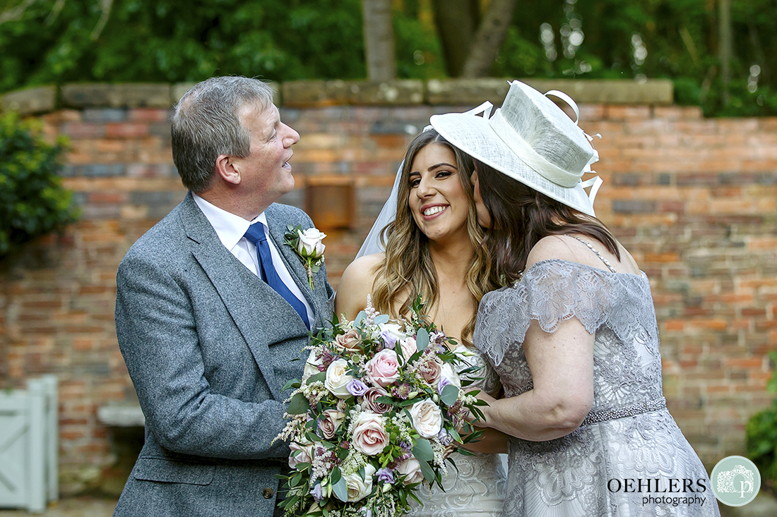 Mum kisses bride's cheek as father looks on.