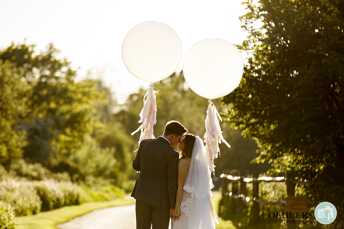 Evening sunlight, romantic contra jour photograph of the couple holding large white balloons and kissing.