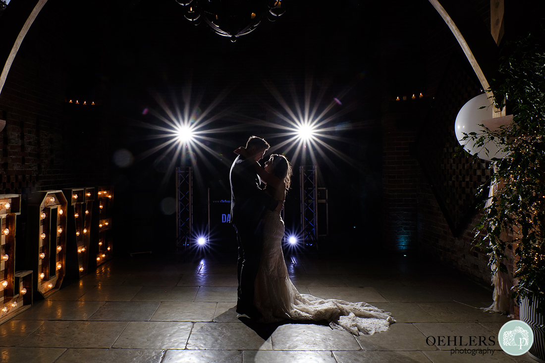 Wedding couple doing their first dance illuminated by large love letters sign and starburst flash.