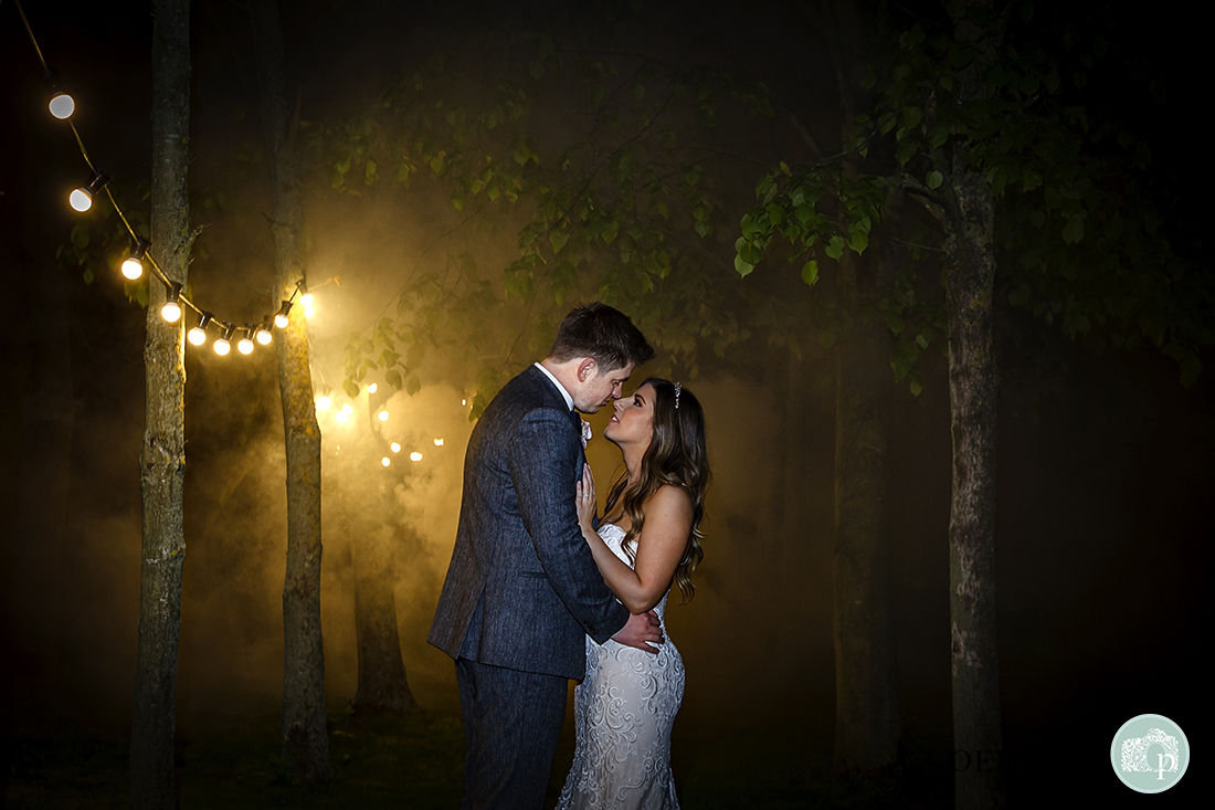 Super-romantic image of the couple gazing into each other's eyes, with misty background lit by fairy lights.