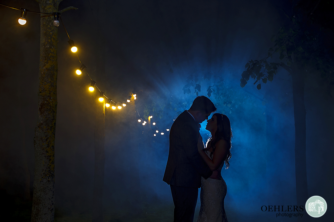 Beautiful silhouetted romantic shot of bride and groom with misty-blue background and fairy lights.