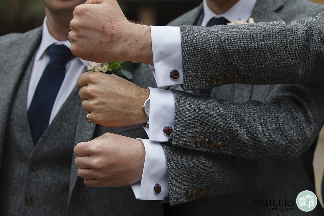 Three arms stacked on top of each other showing wedding cufflinks.