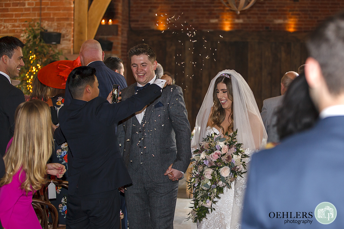 Guest throwing confetti at the bride and groom as they walk back down the aisle.