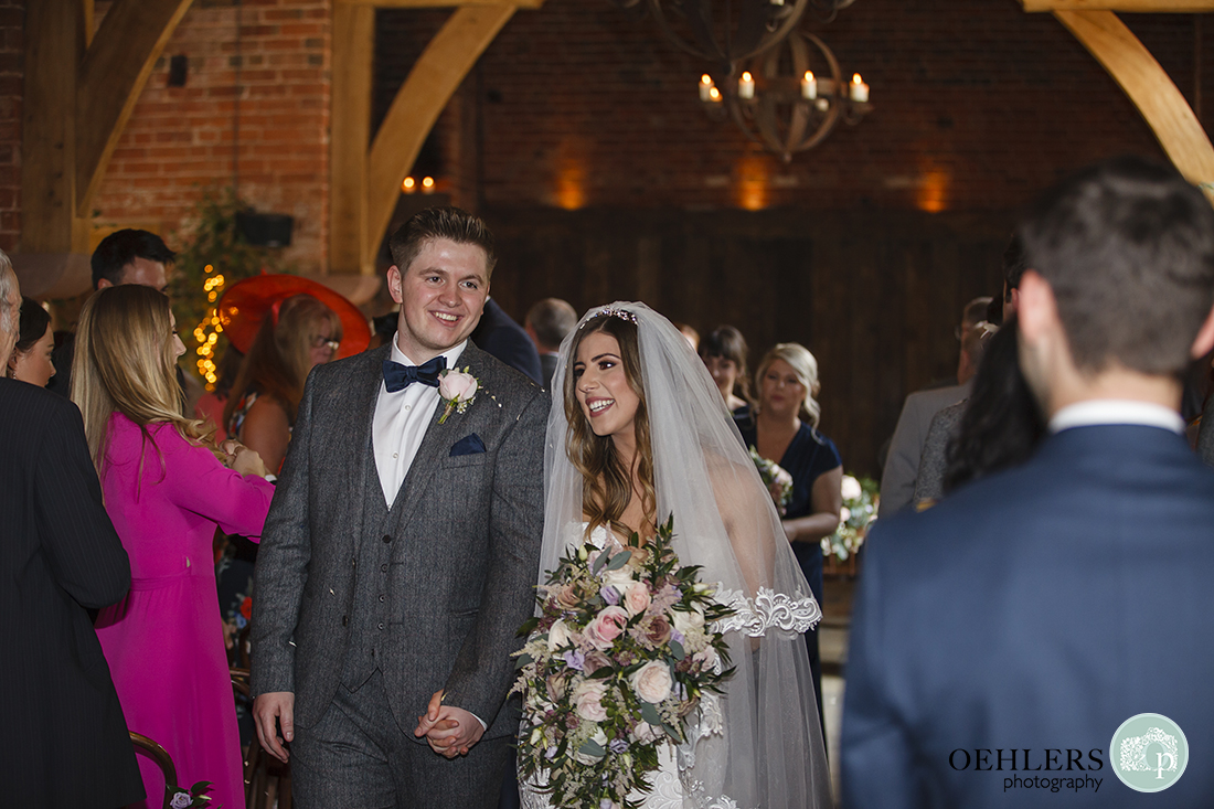 Bride and groom with beaming smiles to their guests as they walk back down the aisle.