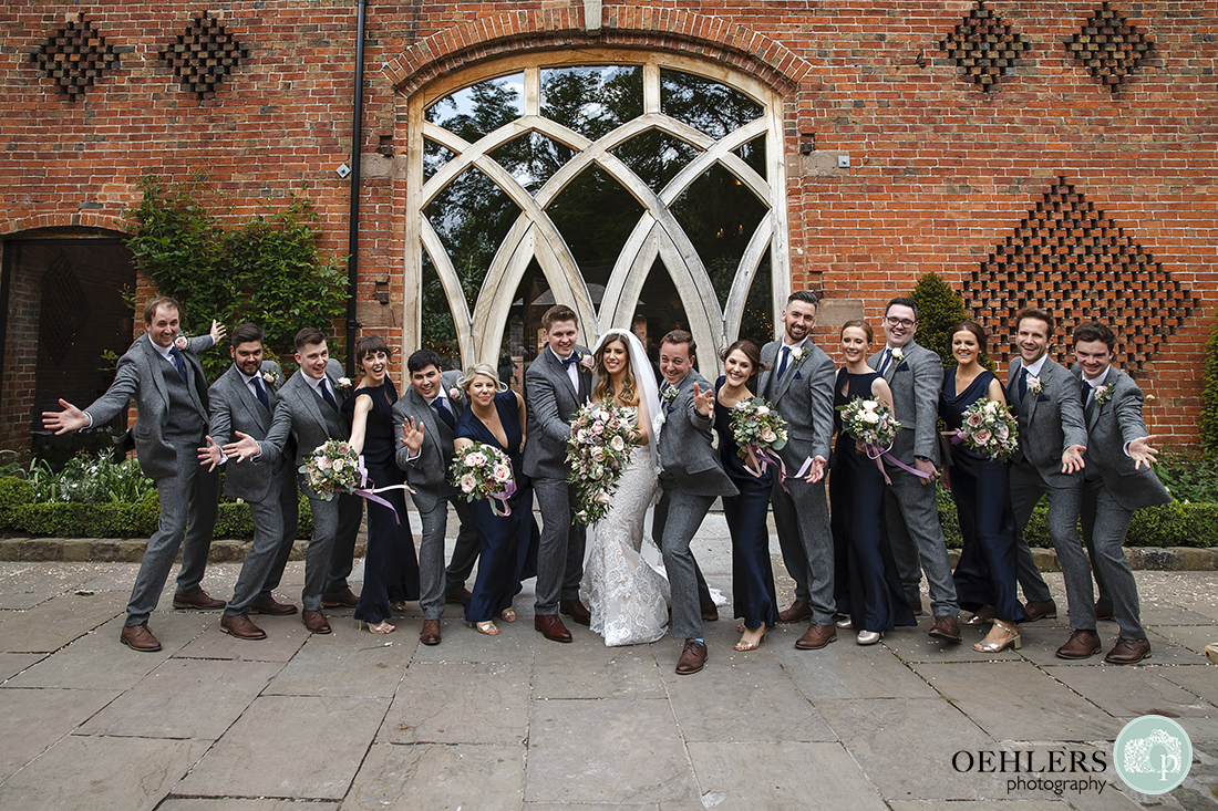Bridal party doing a jazz hands pose in the courtyard.