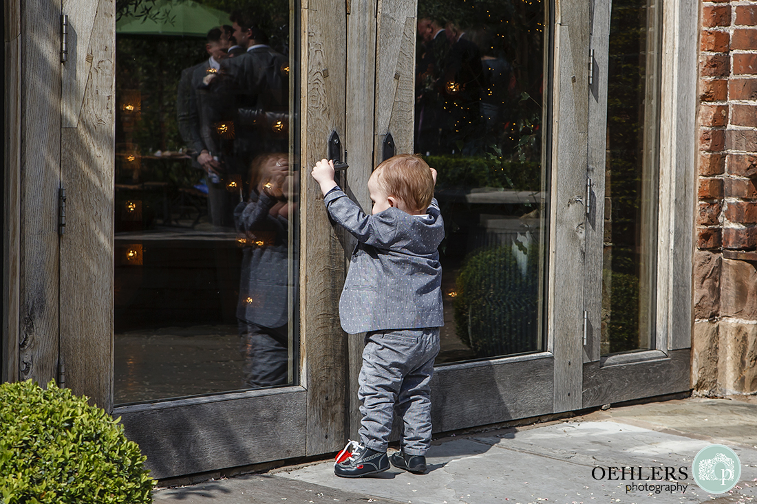 Very young suited wedding guest, driven by hunger, makes an early dash for the doors of the wedding breakfast room.
