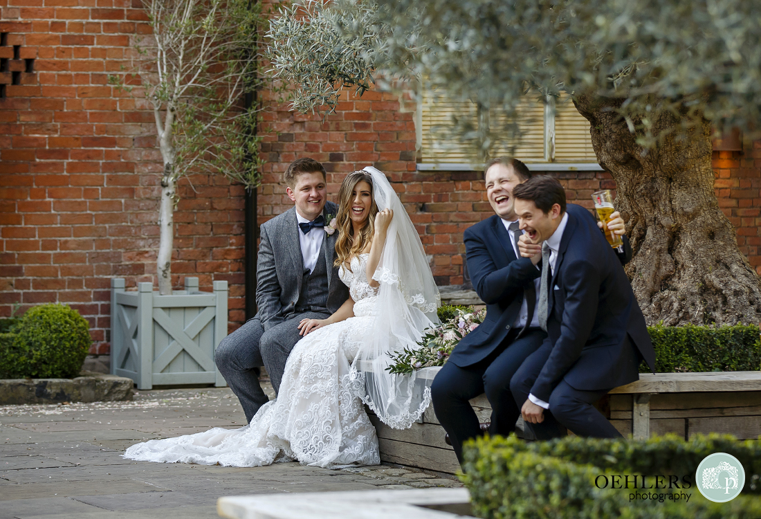Two male guests photo-bombing bride and groom's photoshoot with mock loving embrace of their own.