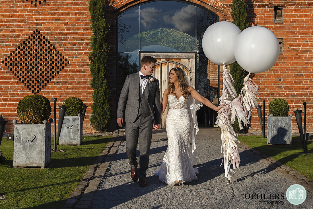 The couple carrying balloons look into each other's eyes, walk along pathway outside Shustoke Barn in evening sunlight.