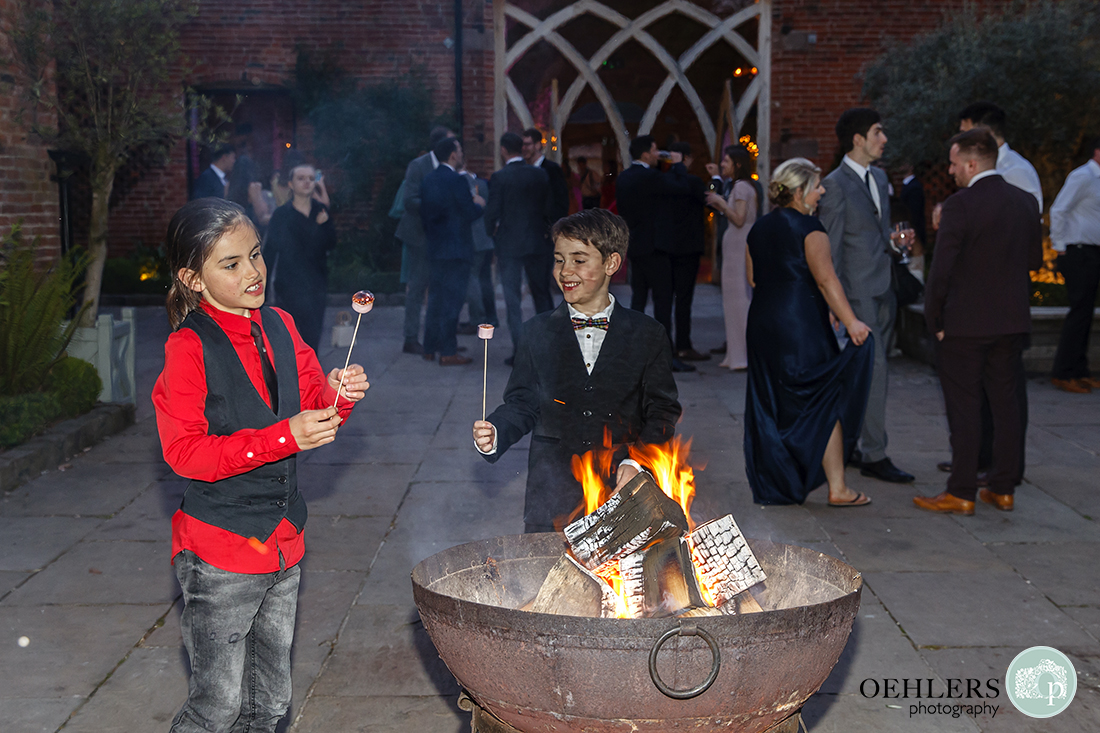 Two young guests enjoying toasting marshmallows over a fire pit in the courtyard in the evening.