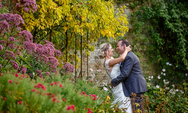 bride gazing into grooms eyes surrounded by beautiful flowers