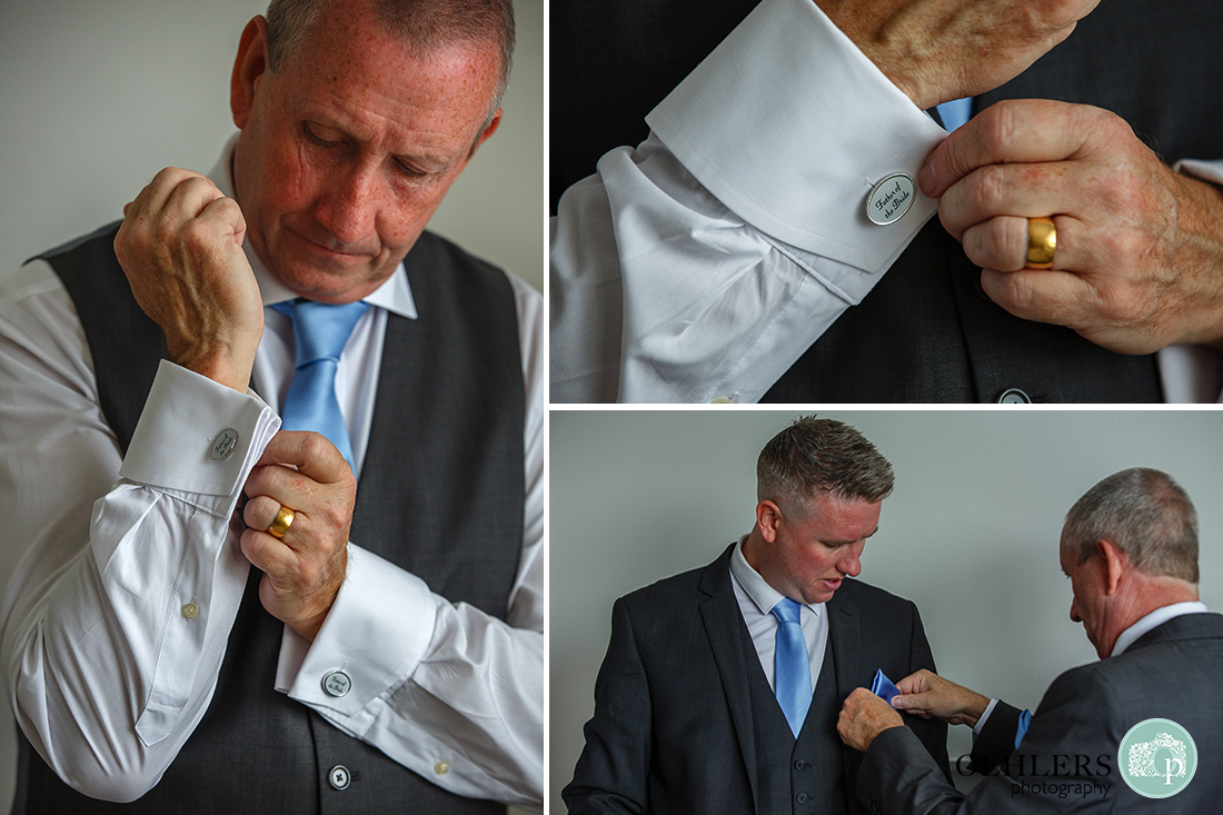 father of the bride putting on his cufflinks and helping his son get ready.