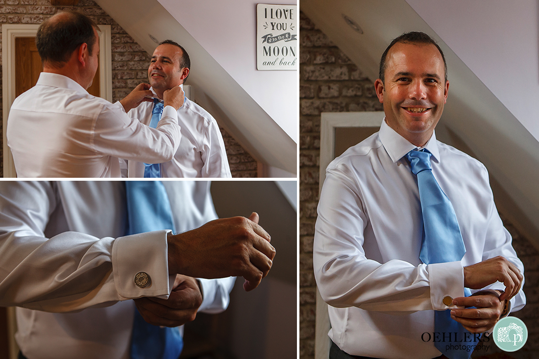 groom putting on his special cufflinks and bestman helping him to get ready