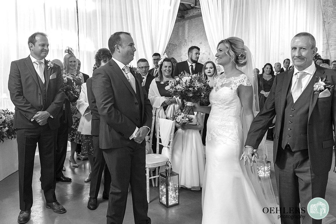 bride smiling at her groom after walking down the aisle with her dad
