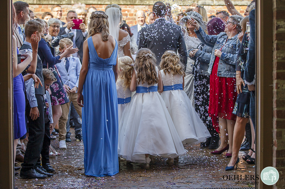 flower girls holding the bridal train as the couple walks outside through the confetti line