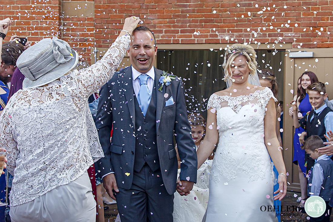 guest pouring confetti over the groom's head whilst bride screws up her face as confetti is chucked at her